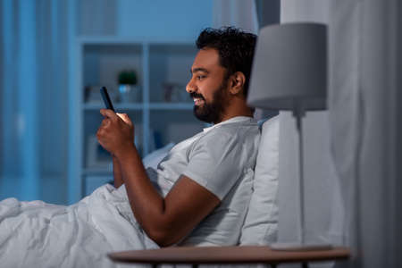indian man with smartphone in bed at home at night 스톡 콘텐츠
