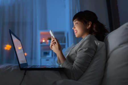 asian woman with smartphone in bed at night 스톡 콘텐츠