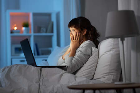 stressed woman with laptop working in bed at night