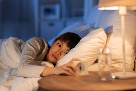 asian woman with clock lying in bed at night