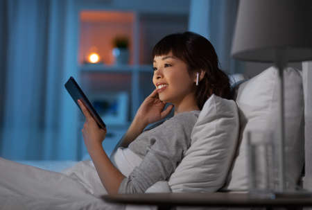 woman with tablet pc in earphones in bed at night 스톡 콘텐츠