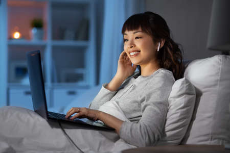 woman with laptop and earphones in bed at night