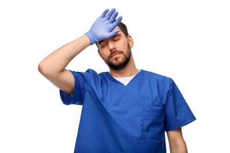 tired doctor or male nurse in blue uniform
