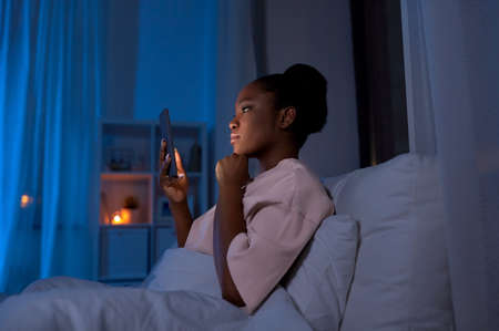woman with smartphone in bed at home at night