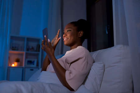 woman with phone having video call in bed at night