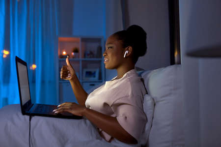 woman with laptop having video call at night