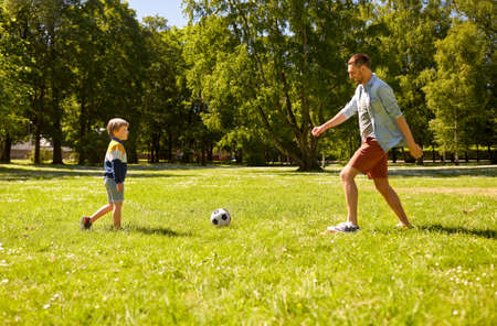 father with little son playing soccer at park