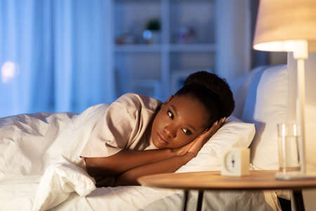 sleepless african woman lying in bed at night 스톡 콘텐츠