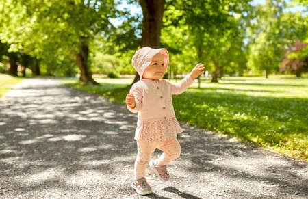happy little baby girl walking in summer park