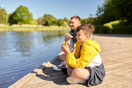 father and son eating sandwiches on river berth
