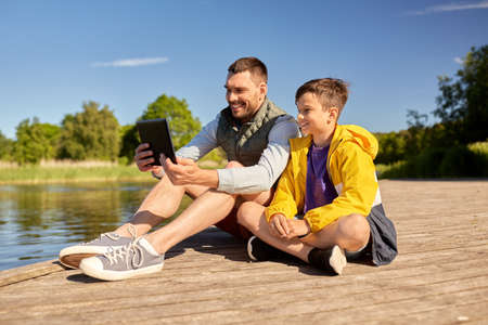 family, generation and technology concept - happy father and son with tablet pc computer sitting on river berth