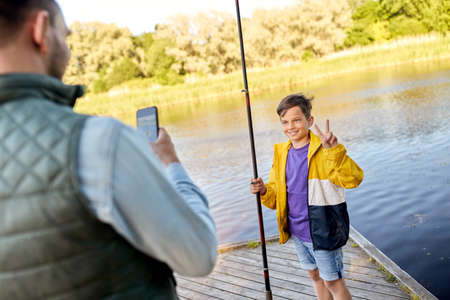 family, generation, summer holidays and people concept - father with smartphone photographing his happy smiling son with fishing rod showing thumbs up on river