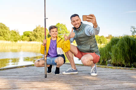 family, generation, summer holidays and people concept - happy smiling father and little son with fishing rods taking selfie with smartphone and showing thumbs up on river 스톡 콘텐츠