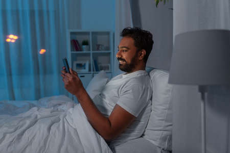 indian man with tablet pc in bed at home at night Standard-Bild
