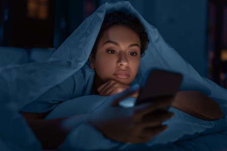 woman with smartphone under duvet in bed at night