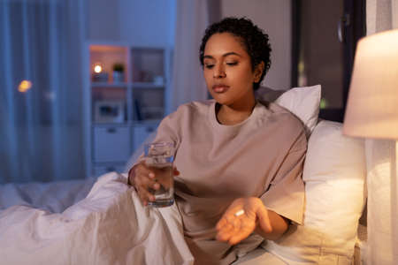 woman with medicine and water in bed at night Standard-Bild