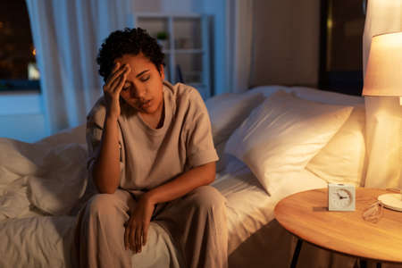 stressed african woman lying in bed at night