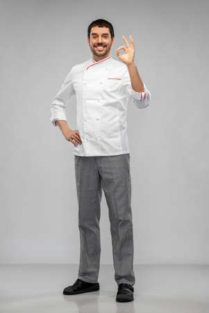 happy smiling male chef showing ok hand sign Standard-Bild