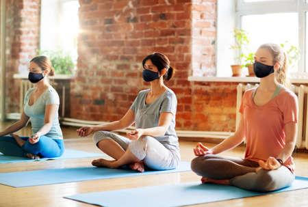 group of women in masks doing yoga at studio
