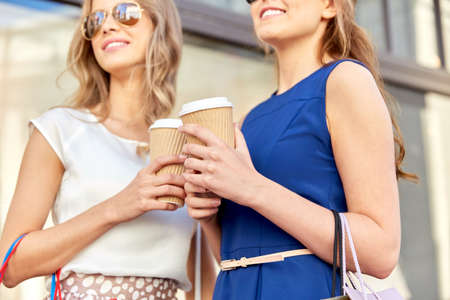 young women with shopping bags and coffee in city