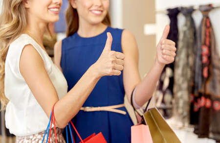 happy women with shopping bags showing thumbs up Standard-Bild