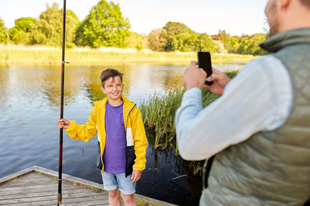 father photographing son with fishing rod on river