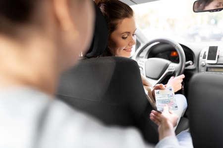 female car driver taking money from passenger