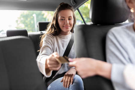 female passenger giving credit card to taxi driver