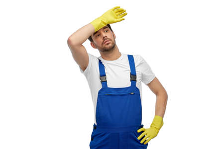 tired male worker or cleaner in overall and gloves Standard-Bild