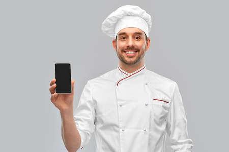 happy smiling male chef showing smartphone Standard-Bild
