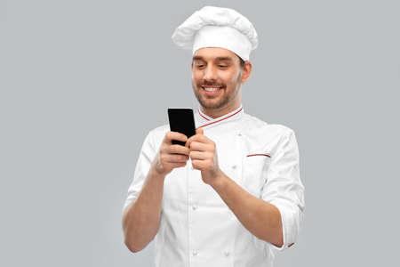happy smiling male chef with smartphone Standard-Bild