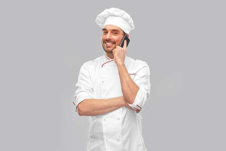 happy smiling male chef calling on smartphone Standard-Bild