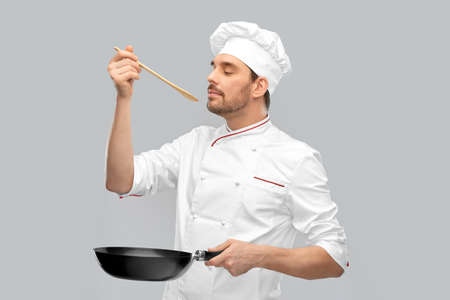 happy male chef with frying pan tasting food