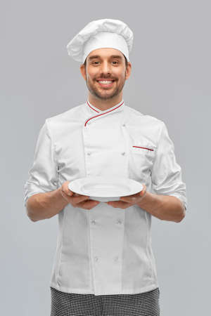 happy smiling male chef holding empty plate
