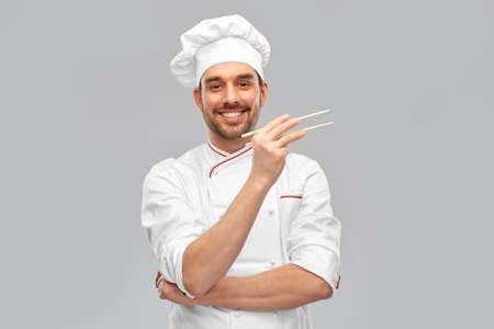 happy smiling male chef with chopsticks Standard-Bild