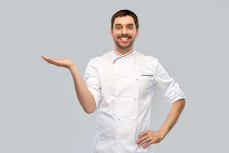 happy smiling male chef holding something on hand