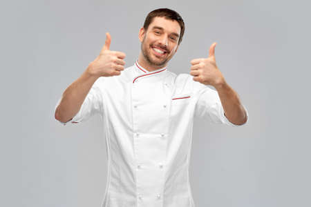 smiling male chef in jacket showing thumbs up Standard-Bild