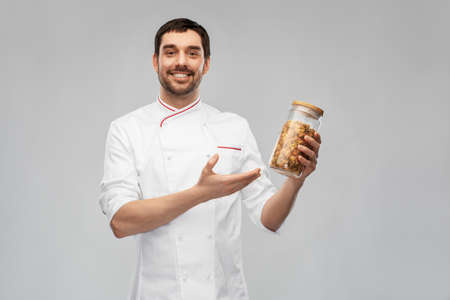 happy smiling male chef with pasta in glass jar