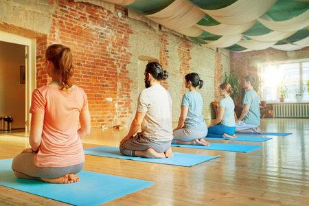 group of people doing yoga kneeling pose at studio