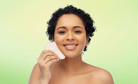 happy woman massaging her face with gua sha tool