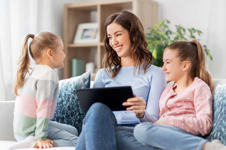 happy mother and daughters with tablet pc at home