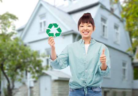 smiling asian woman holding green recycling sign