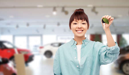 happy asian woman holding car key with green leaf