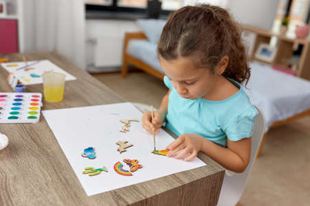 little girl painting wooden items at home Standard-Bild