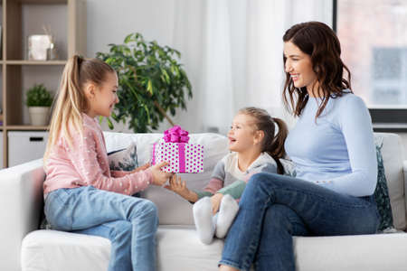 girl giving present to younger sister at home Stock Photo