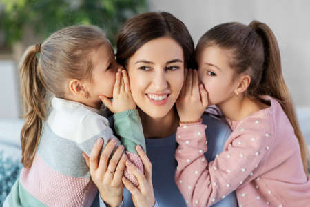 happy mother and daughters gossiping at home