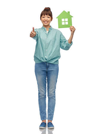 asian woman with green house showing thumbs up