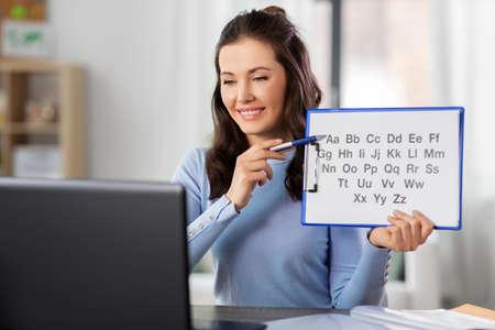 teacher with alphabet having online class at home