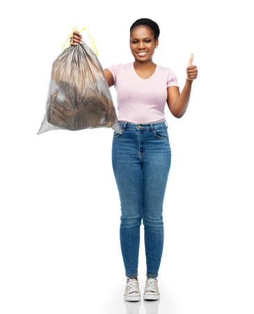 smiling woman holding plastic trash bag with waste