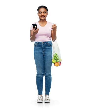 woman with smartphone and food in string bag